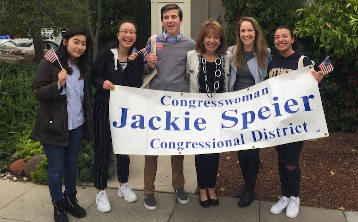 "Five students with congresswoman holding up sign and American Flags, sign says ""Congresswoman Jackie Speier Congressional District"""